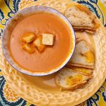 bowl of cream of tomato soup topped with croutons and side of grilled cheese