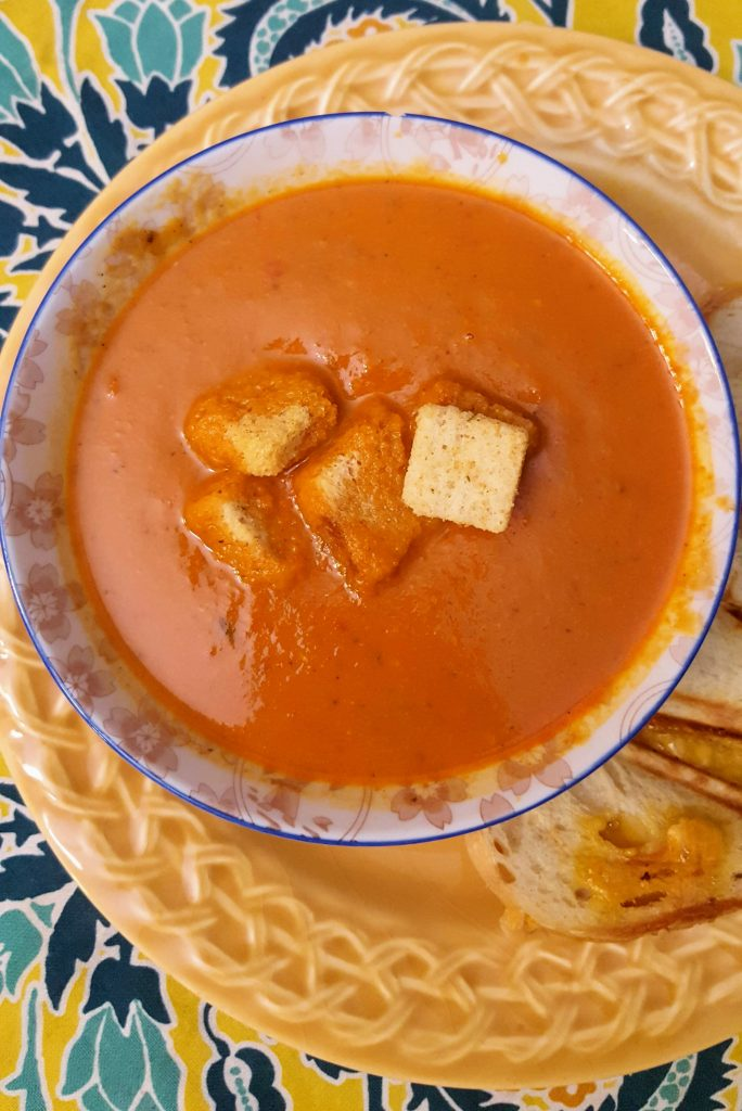 bowl of cream of tomato soup topped with croutons